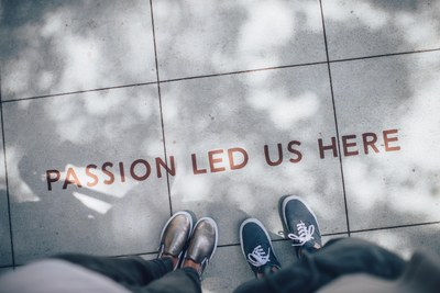 """The camera tilts down to look at tiled pavement. Two pairs of feet surround the words """"Passion led us here"""""""